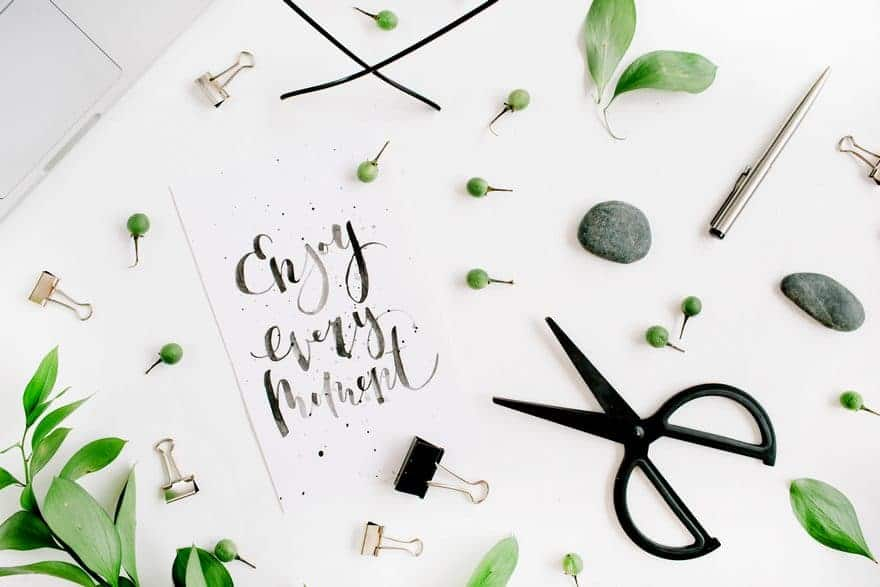 Enjoy every moment motivational quote on a white desk