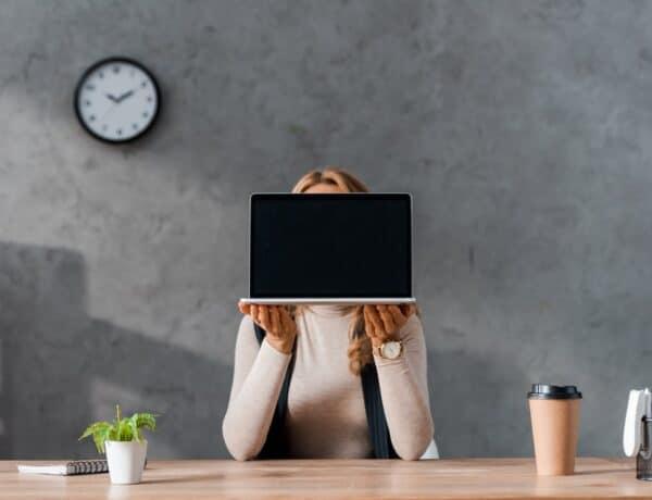 Woman giding her face behind a laptop
