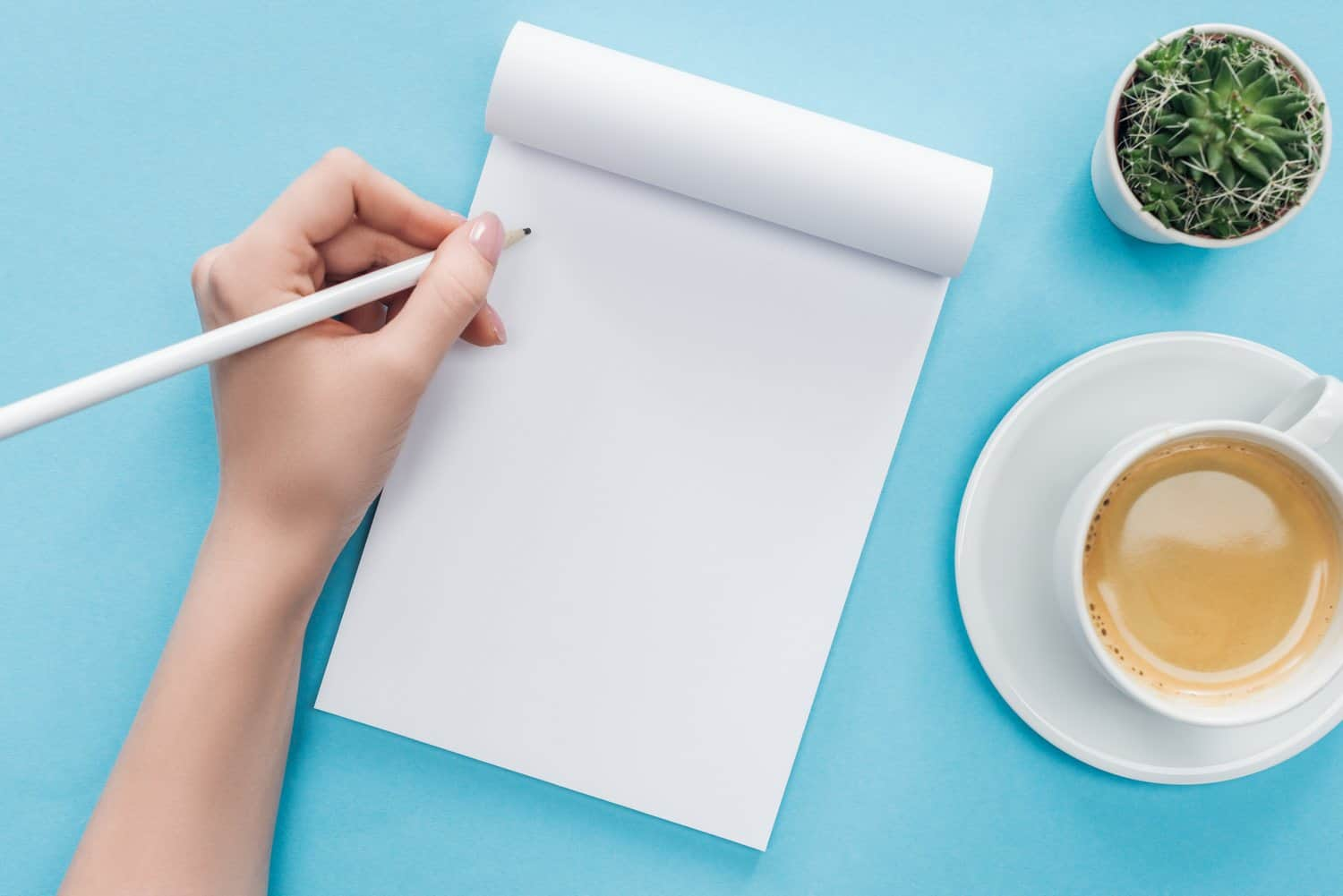 Woman's hand writing on a notepad next to a coffee cup