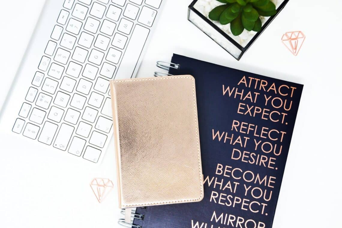 A motivational text on a black notebook next to a keyboard, a succulent and a golden notebook