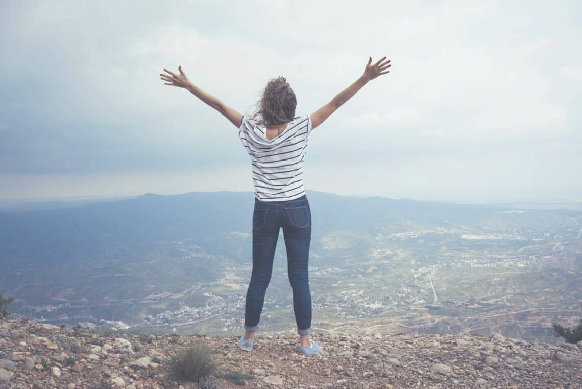 Powerful woman standing on the top of a mountain arms wide open